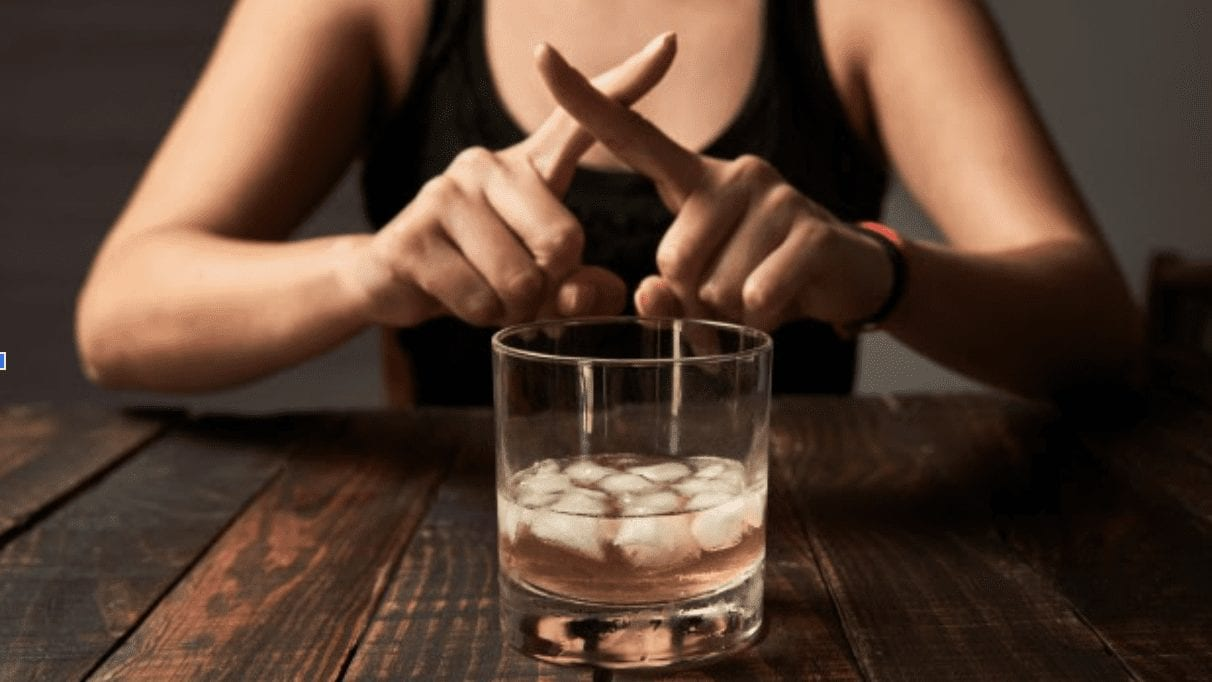 Glass of alcohol, girl making cross with fingers in front of it