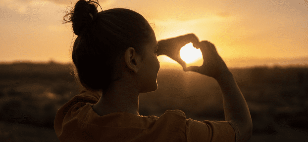 woman making a heart with her hands at the sun